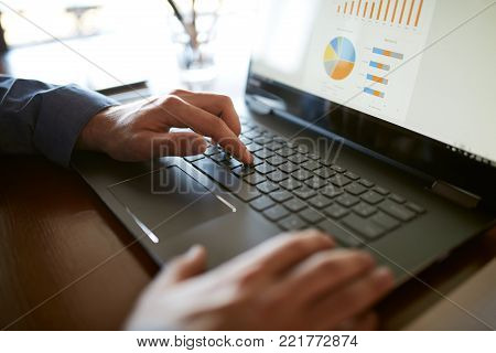 Close-up back view of caucasian businessman hands typing on laptop keyboard and using touchpad. Notebook and pen on foreground of workspace. Charts and diagrams on screen.