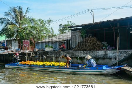 Soc Trang, Vietnam - Feb 2, 2016. People selling flowers on Mekong River in Soc Trang, Vietnam. Mekong is the longest river in Southeast Asia, the 7th longest in Asia.