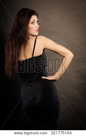 Party celebration concept.  Magnificent long hair woman red lipstick wearing black evening dress on dark back view