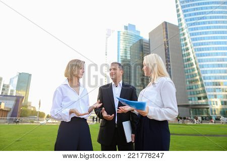 Financial analysts talking about crypto currency with tablet in  . Concept of  managing various aspects of money and speaking with boss. Colleagues speaking outside and smiling.