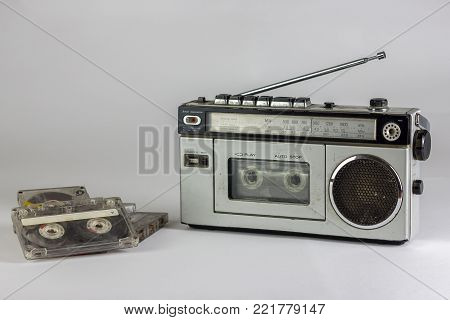 old radio and cassette recorder with cassettes isolated on white background