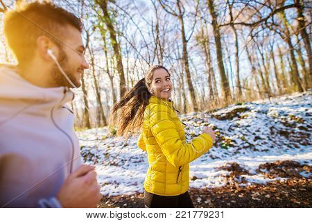 Active fit sportive couple running with strong persistence through the forest in the winter morning.