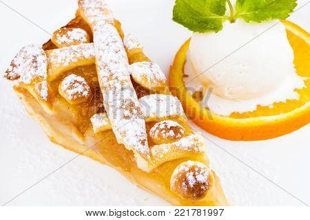 Apple pie with vanilla ice cream on white plate