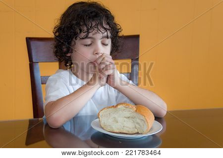 Child praying for the daily bread:Curly-haired boy sits and prays with eyes closed and hands together before eating a piece of bread placed before him on the dining table.
