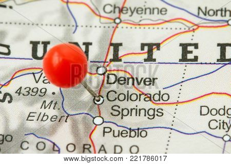 Close-up of a red pushpin in a map of Colorado Springs, USA.