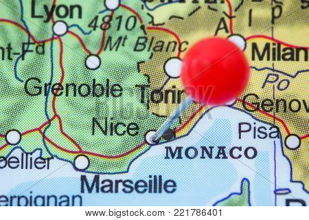 Close-up of a red pushpin in a map of Nice, France.