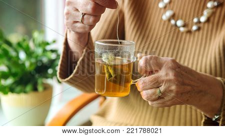 older woman hand holding a glass of tea with teabag