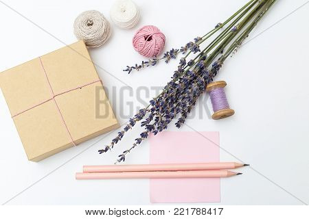 Preparation for the holiday. Bouquet of lavender and gift box on a white background. Flat lay