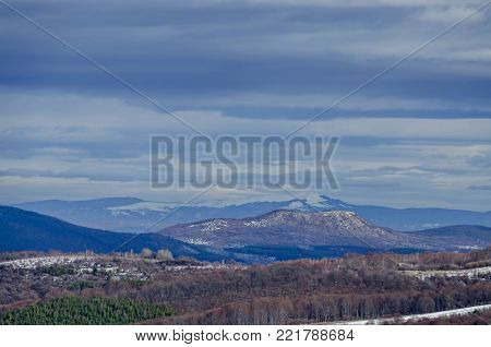 Majestic view of cloudy sky, winter mountain, snowy glade, conifer and deciduous forest from Plana mountain   toward Balkan mountain or Stara planina, Bulgaria, Europe