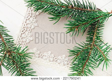Blank greeting paper card decorated lace ribbon and natural green fir tree boughs.