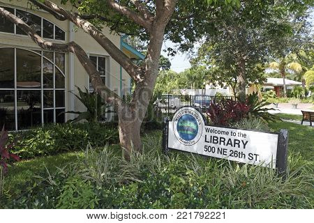 Wilton Manors, FL, USA - August 25, 2017: Building front and Welcome to the Library sign at 500 NE 26th St. Summer day Wilton Manors Library exterior and sign.