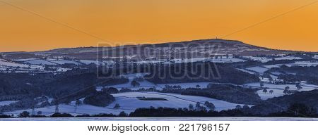 Panoramic View Of Shropshire Hills Covered In Snow With Vivd Yelow Cloudless Twilight Sky