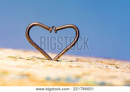 a heart of curved nails on a blue background, a symbol of overcoming difficulties