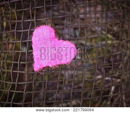 Colorful decorative heart on old rustic iron sieve background.