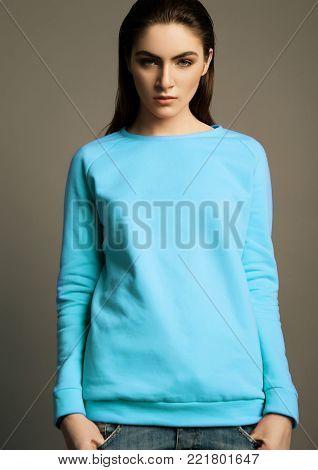 Beautiful fashion model with ligh blue cyan jumper on grey background