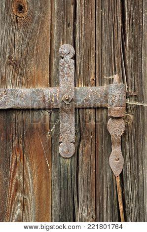 Ancient door with steel hinge and cobwebs.
