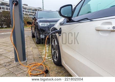 Kijkduin, The Hague, the Netherlands - 13 January 2017: hybrid electric cars charging with electric plug in power station