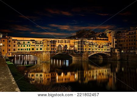 Florence, Tuscany, Italy: view at night of the landmark Ponte Vecchio, the famous medieval bridge over the Arno river with old shops of artisan goldsmiths and jewelers