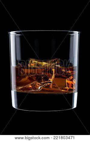 Elegant glass of whiskey with ice cubes isolated on black background