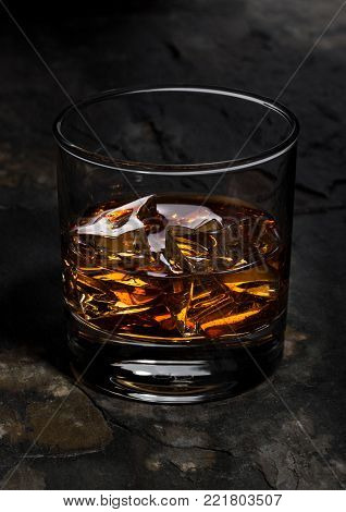 Elegant glass of whiskey with ice cubes on stone background