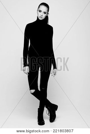Young beautiful fashion model wearing black polo neck jumper and jeans on grey background. Black and White