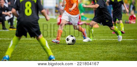 Kids Playing Football Soccer Game on Sports Field. Boys Play Soccer Match on Green Grass. Youth Soccer Tournament Teams Competition. Running Youth Football Players