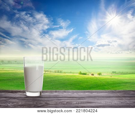 Glass of fresh milk against wavy green pasture. The concept of natural food.