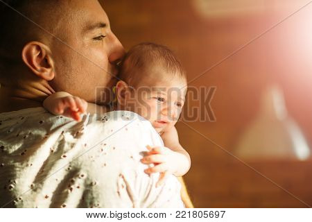 Sweet baby boy on daddy shoulder, father talking on phone