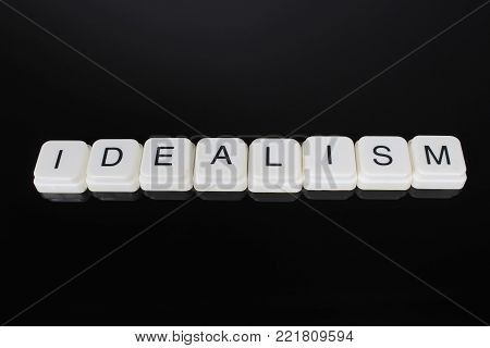 Idealism text word title caption label cover backdrop background. Alphabet letter toy blocks on black reflective background. White alphabetical letters. White educational toy block with words on mirror board table.