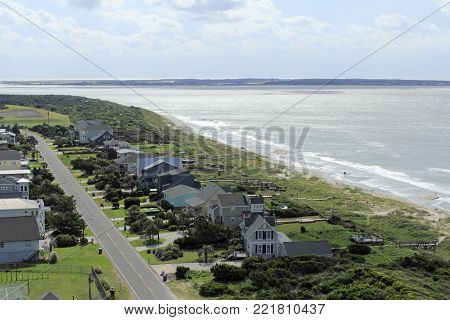 Fort Caswell and Bald Head Island seen from a high view on a sunny day. Scenic high view of the Atlantic Ocean seascape and landscape with homes of Caswell Beach