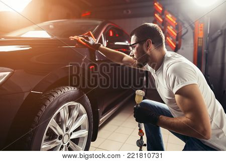 A man cleaning car with microfiber cloth, car detailing or valeting concept. Selective focus.