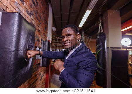 man wearing business suit and boxing gloves. African man in classic suit and Boxing gloves strike. looking at camera