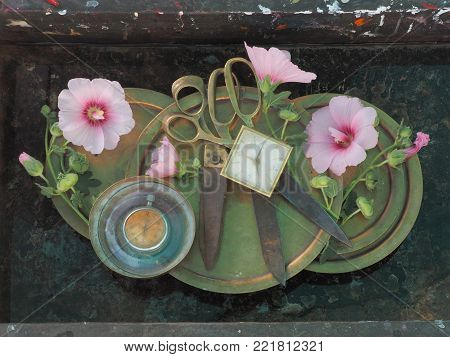 Pair of metal scissors on a copper dish with clock faces adorned around the edges of pink delicate mallow flowers, modern interior design of the walls.