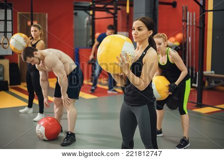 Cross fit ball fitness workout group woman and man at gym. camera focus in the ball.