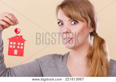 Young happy woman doing bubble with chewing gum while holding new house key with red home shape. Real estate housing and happiness concept.