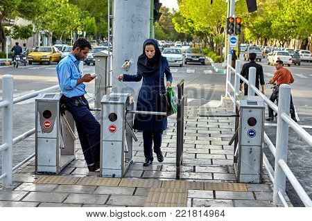 Isfahan, Iran - April 23, 2017: A woman in Islamic clothes passes to the bus stop through the control turnstile.