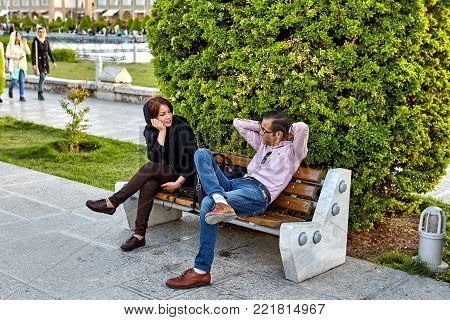 Isfahan, Iran - April 23, 2017: A young couple is resting, sitting on a bench in the square of Naghshe Jahan.
