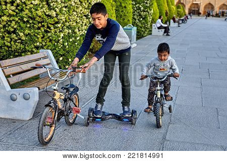 Isfahan, Iran - April 23, 2017: Two brothers ride bicycles and electric skateboard in the square Naghshe Jahan.