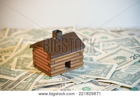 Toy Log Cabin House sitting on a pile of Money (us dollars)