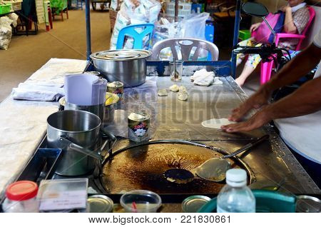 Thai People Cooking Desert Snack Roti With Banana And Egg, Drizzled With Sweetened Condensed Milk Fo