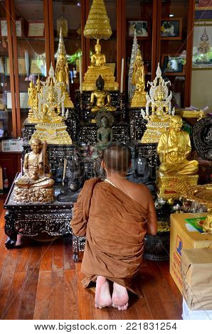 Thai monk praying and respect buddha statue in church or ubosot of Wat Amphawan on November 7, 2015 in Sing Buri, Thailand