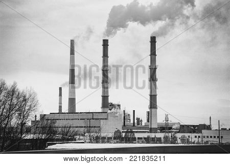 Smoking chimneys of the plant. Fuming chimney of a factory. Black and white photo