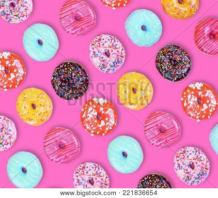 assorted variety of doughnuts on a yellow background studio shot overhead
