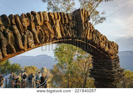 Sydney, Australia - Apr 18, 2017: Stone archway of the Honeymoon Lookout, with viewing platform and tourists. Overlooking Jamison Valley. Katoomba, Blue Mountains National Park - UNESCO Heritage Site.