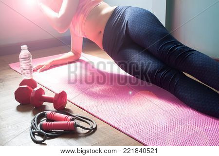 Fit young woman wearing sport wear doing side plank, workout at home, Healthy and diet concept