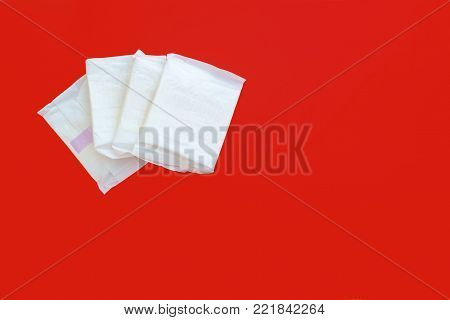 Feminine sanitary napkin, an absorbent item worn by a woman while menstruating, on red background with copy space for hygiene and health concept