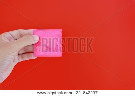 Hand holding male condom on red background with copy space for contraception and safety sex concept