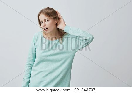 Body language. Portrait of young excited Caucasian blonde woman with long hair in blue sweater looking at the camera opened mouth and holding hand behind her ear while listening with excitement to incredible story