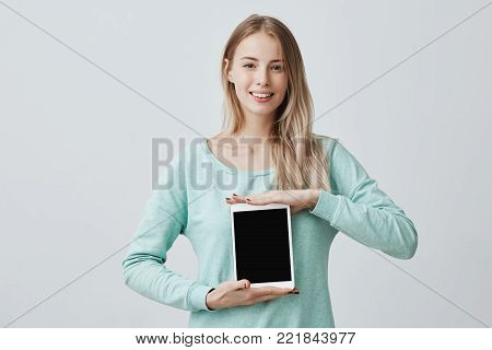 Beautiful blonde female dressed casually holds digital tablet with copy space for your text or advertisement. Isolated portrait of good-looking young fair-haired smiling woman with tablet