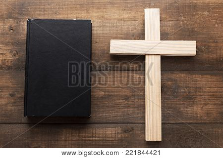 A big wooden cross next the closed Holy Bible. A black book on a wooden surface. The way to God through prayer.